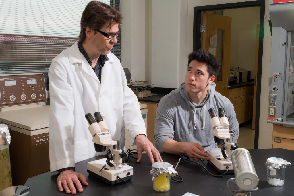 Student and professor in lab with microscopes